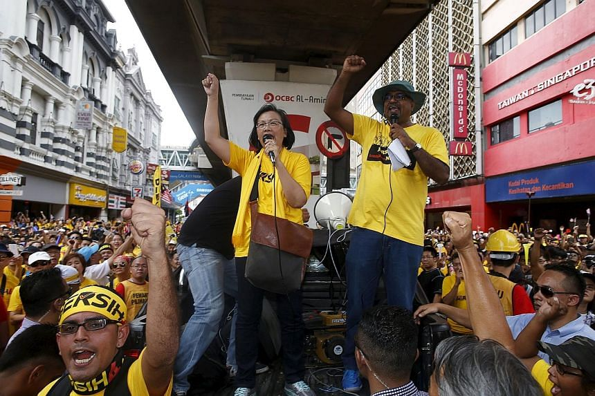 Clockwise from right: Malaysia's ex-PM Mahathir Mohamad and his wife Siti Hasmah dropped in on the Bersih event yesterday; the group's chairman Maria Chin Abdullah rallying the supporters; Wan Azizah (in sunglasses), the wife of jailed opposition lea