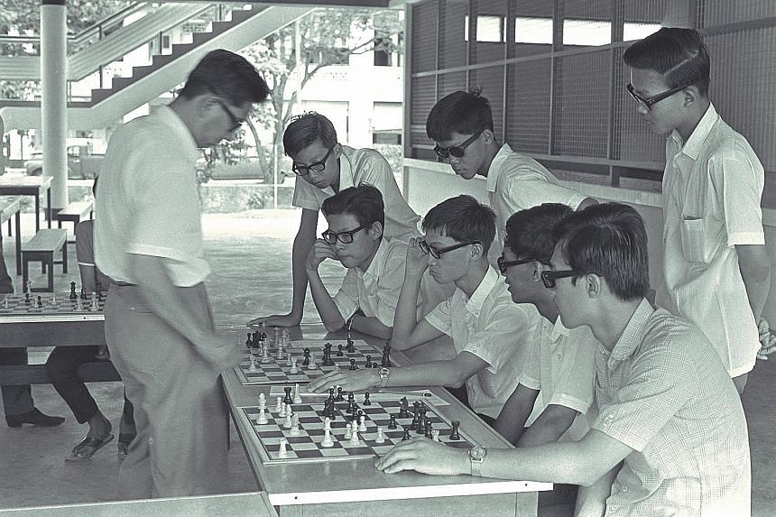 Professor Lim Kok Ann (left) pitted against more than 20 schoolboys in a chess game at the Tanjong Katong Technical School. Last in a series of displays for junior members of the Singapore Chess Olympiad, it was to raise funds to send a team to the n