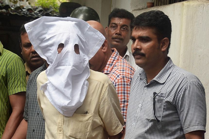 Police escorting Sanjeev Khanna (face covered), the former husband of Indrani Mukerjea who is accused of murdering her daughter Sheena Bora in 2012, to court in Kolkata last Thursday. Khanna is alleged to have been involved in the murder.