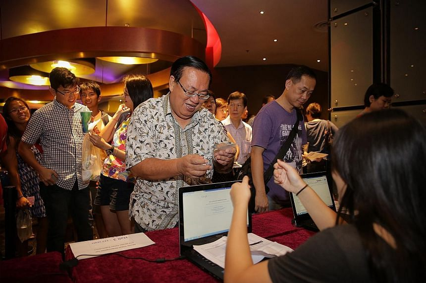 Mr John Lim, 66, collecting his complimentary tickets to 7 Letters at the Golden Village cineplex at VivoCity yesterday.