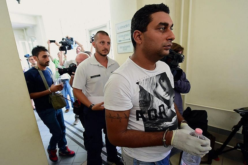 Two of the four suspects (handcuffed, each carrying a bottle of water) are led by a Hungarian police official into the Kecskemet courtroom yesterday. German Chancellor Angela Merkel has said that the migration crisis is a bigger test for the European