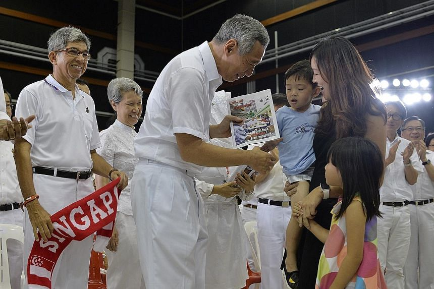 PM Lee handing a copy of the manifesto to housewife Angeline Liu, 32, and her children, three-year-old Kaleb and six-year-old Faith. With them are (from left) Communications and Information Minister Yaacob Ibrahim, Mr Lee's wife Ho Ching, Manpower Mi
