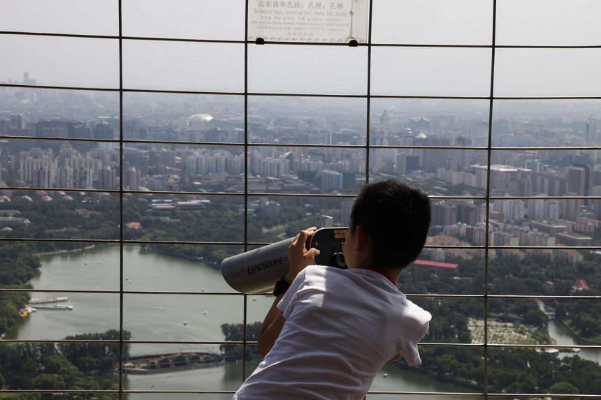 A child using a telescope to view city districts from a tourist viewing tower in Beijing on Aug 25, 2015.
