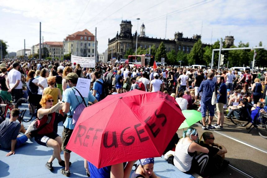 """An anti-racism protester holds an umbrella with the lettering """"Refugees Welcome"""" during a rally on Aug 29, 2015 in Dresden, Germany."""