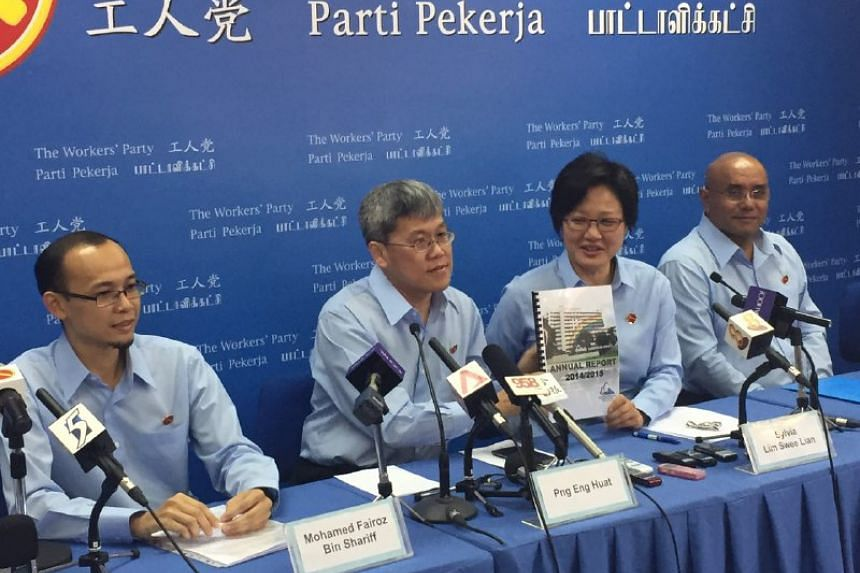 Workers' Party chairman Sylvia Lim (second from right) and MP Png Eng Huat (second from left) hold up a copy of the annual Aljunied Hougang Punggol East Town Council report for FY2014/2015 during a press conference on Aug 30, 2015. With them are WP e