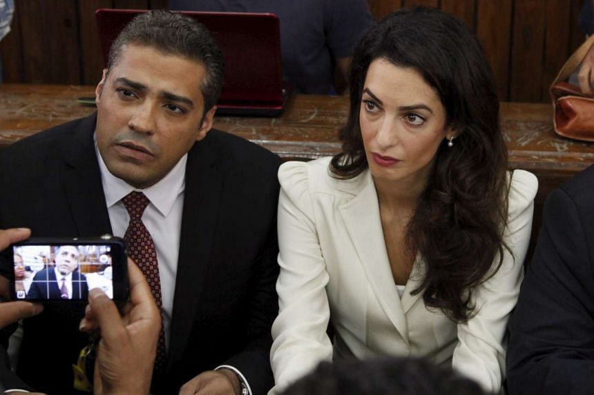 Al Jazeera journalist Mohamed Fahmy and his lawyer Amal Clooney look on before hearing the verdict.