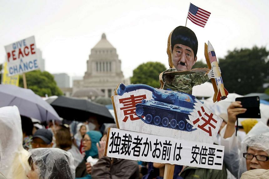 A protester holds a caricature cut-out of Japan's Prime Minister Shinzo Abe during a mass rally against his security bill outside the parliament in Tokyo on Aug 30, 2015.
