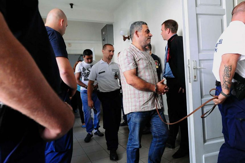 Hungarian police lead a man, suspected to be involved in the death of 71 migrants in a truck in Austria, into Kecskemet courtroom on Aug 29, 2015.