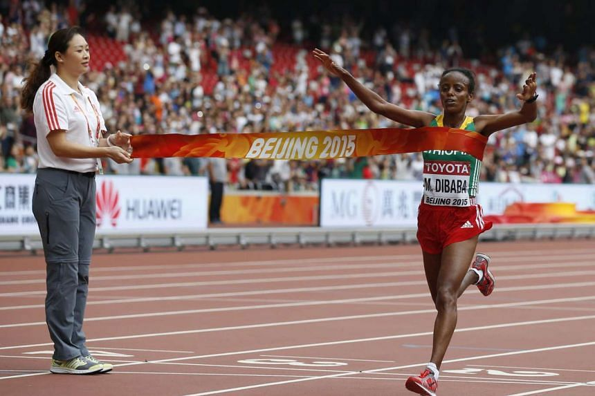 Mare Dibaba of Ethiopia crosses the finish line first to win the women's marathon at the 15th IAAF Championships at the National Stadium in Beijing, China on Aug 30, 2015.