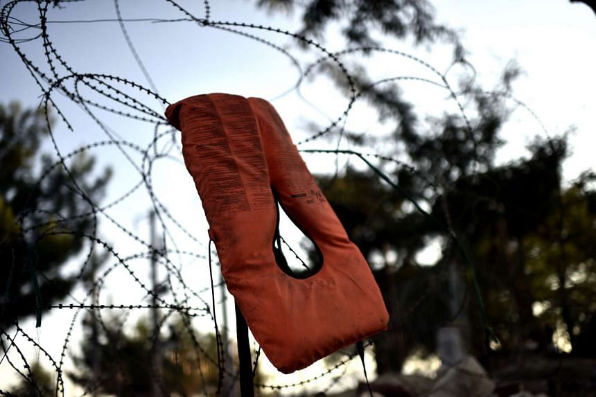 A life vest is placed on a barb wire at the Greece - Macedonian border line on Aug 29, 2015. The EU is grappling with an unprecedented influx of people fleeing war, repression and poverty in what the bloc has described as its worst refugee crisis in