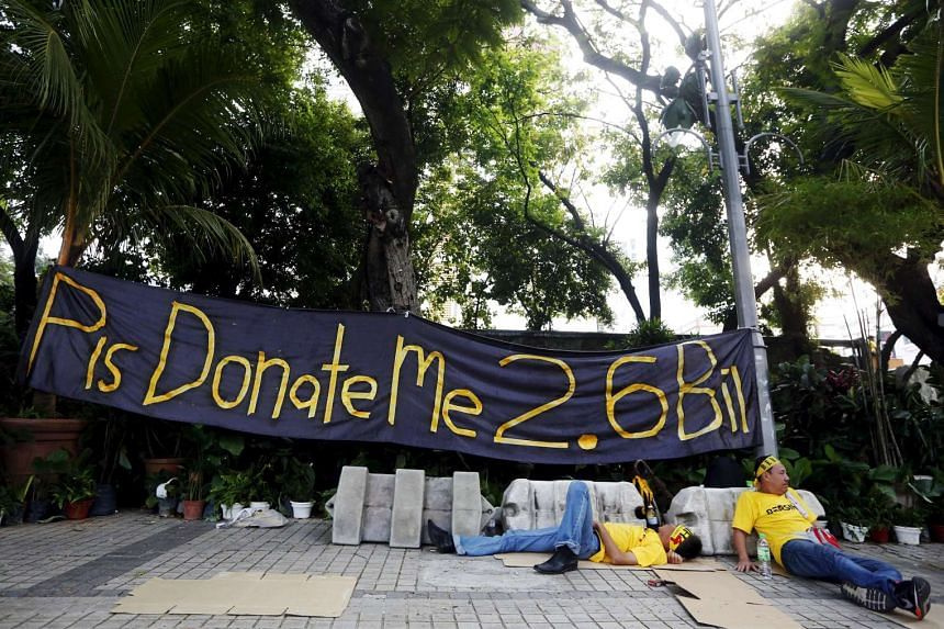 Protesters rest in front of a banner during a rally organised by pro-democracy group Bersih (Clean) in Malaysia's capital city of Kuala Lumpur, on Aug 30, 2015.