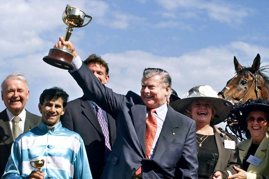 Trainer Bart Cummings lifts the Melbourne Cup after Rogan Josh (horse, on right) won the Melbourne Cup at Flemington Race Course in Melbourne, on Nov 2, 1999.