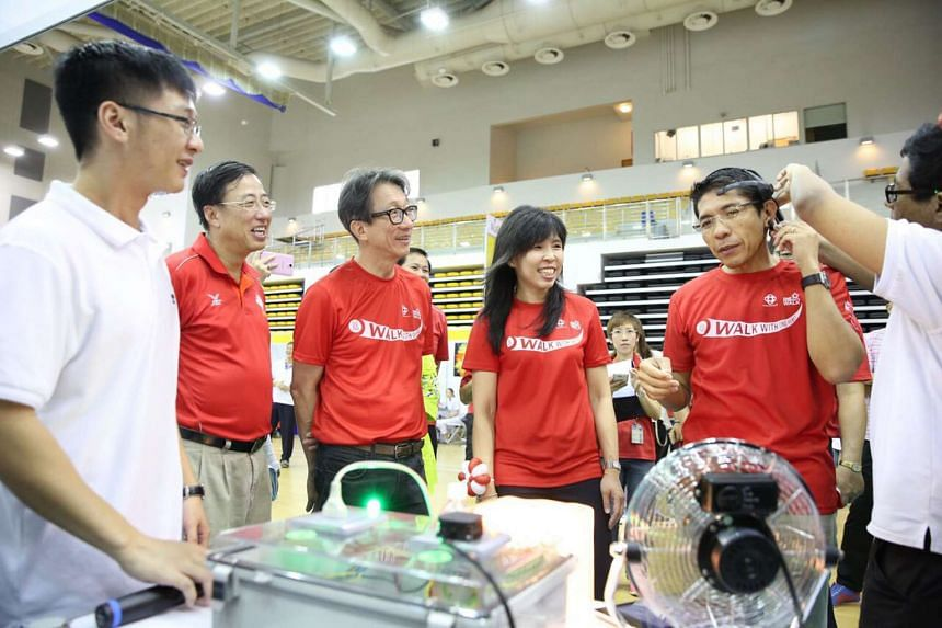 Minister of State for National Development and for Defence Maliki Osman (right) trying on a headset that enables him to turn on the power flow to a socket during the ITE Fiesta at ITE College East. He is accompanied by (from second left) ITE director