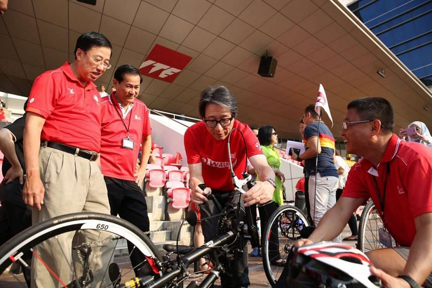 (From left) ITE director and CEO Bruce Poh, ITE College East deputy principal (Academic) Lim Teck Lee, Manpower Minister Lim Swee Say and ITE East physical education section head Kang Jau Yew inspecting a handcycle used in Cycle50 Wheels for Wheels.