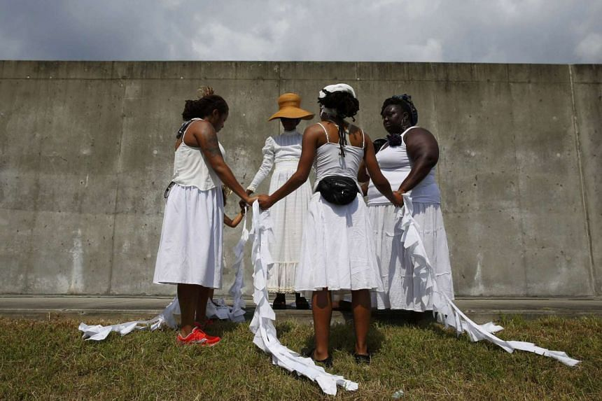 Women pray at the site of the 2005 Industrial Canal levee failure, during a ceremony marking the 10th anniversary of Hurricane Katrina in the Lower Ninth Ward in New Orleans, Louisiana on Aug 29, 2015.