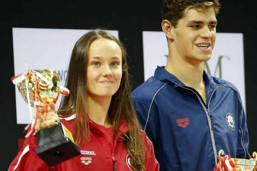 Turkey's Viktoria Gunes (left) and Michael Andrew of the US standing on the podium after they were give awards for the best female swimmer and best male swimmer respectively at the 5th Fina World Junior Swimming Championships at the OCBC Aquatic Cent