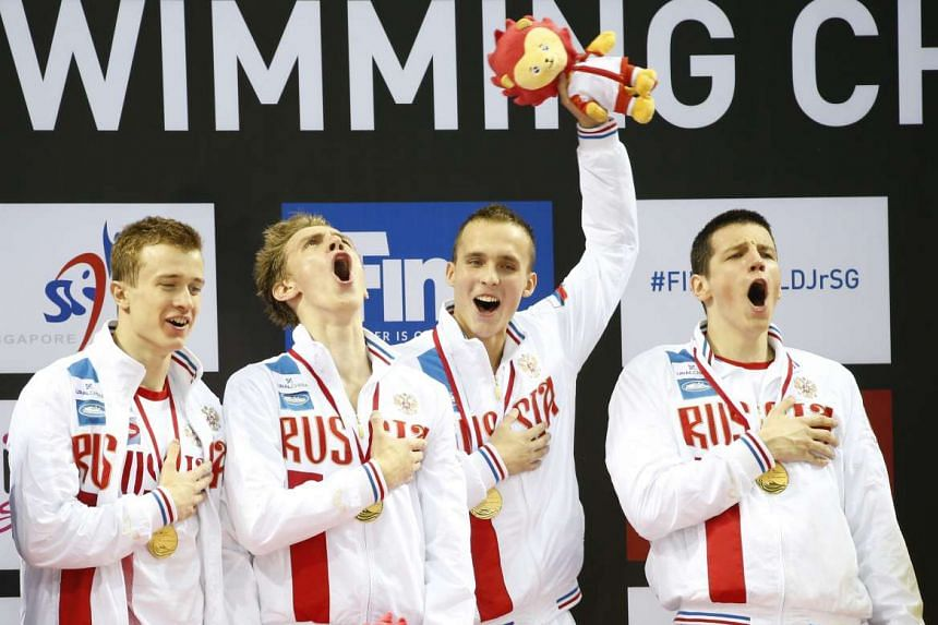 The Russian quartet of (from left) Vladislav Kozlov, Daniil Pakhomov, Anton Chupkov, and Roman Larin singing the national anthem after breaking the world record on their way to the gold in the 4x100m men's freestyle relay at the OCBC Aquatic Centre o