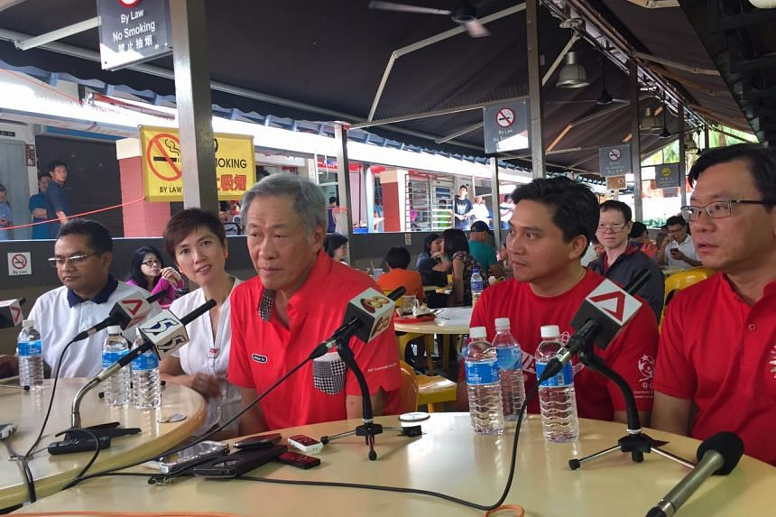 Dr Ng Eng Hen, flanked by his running mates from Bishan-Toa Payoh GRC, at a coffee shop in Block 280 Bishan St 24 on Sunday.
