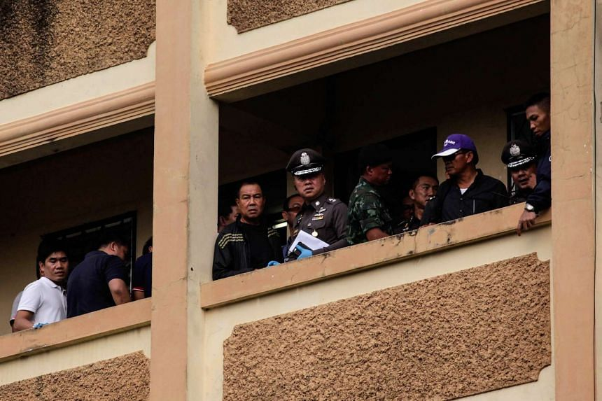Somyot Poompanmoung, Lieutenant General of the Thai police (centre) stands with other police officers on the balcony of an apartment block as a suspect of the Bangkok shrine bombing is detained, in Nong Chok, Thailand, on Aug 29, 2015.