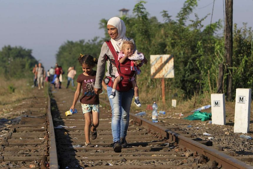 Syrian migrants walk along a railway track after crossing into Hungary from the border with Serbia near Roszke on Aug 29, 2015.
