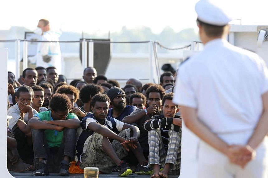 Migrants wait to disembark from a Coast Guard ship in the Sicilian harbour of Messina, Italy on Aug 29, 2015.