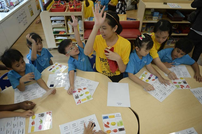 Educators playing bingo with children at a kindergarden.