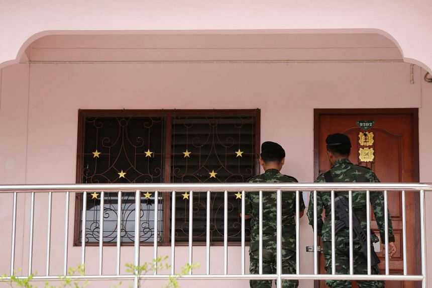 Thai soldiers examine next to a residence during a joint force military and police operation searching rented rooms where believed to be linked with the arrested foreign suspect at a Muslim community of Mimuna Garden Home apartment in Minburi distric