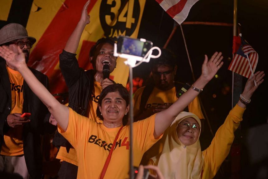 Malaysian Bar Council president and former Bersih co-chair Datuk Ambiga Sreenevasan (left) and Leader of opposition party Pakatan Rakyat and wife of imprisoned former deputy Prime Minister Anwar Ibrahim, Wan Azizah Wan Ismail (right), wave the crowd