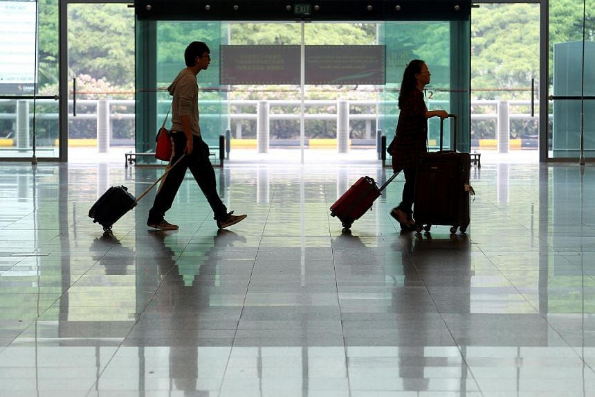 Two passengers pulling their luggages at the departure hall of Changi Airport Terminal 2.
