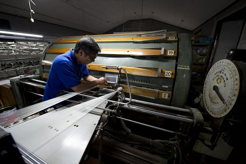 A factory worker inspects the quality of material on a weaving machine at the Gen Maeda silk weaving factory in Fujiyoshida city, Japan on Aug 26, 2015.