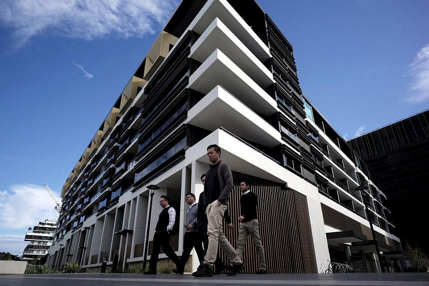 Sydney residents walk past a newly-completed apartment development in Sydney's inner-city suburb of Zetland.
