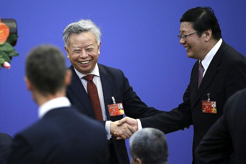 Mr Jin Liqun (centre), seen here in a file photo shaking hands with China's Finance Minister Lou Jiwei, is ready to face the challenges of his new role as president of the Asian Infrastructure Investment Bank.