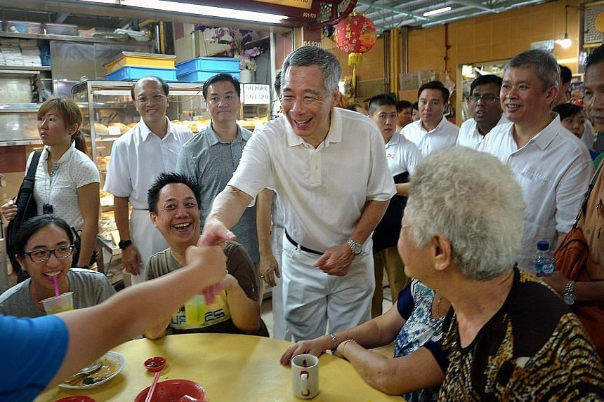 PM Lee greeting residents at the Cheng San market in Ang Mo Kio Avenue 10, as he led the Ang Mo Kio GRC candidates in three market visits.