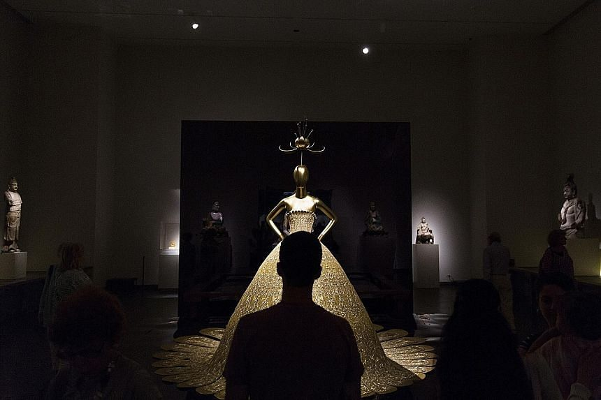 A visitor photographs a Dior dress by John Galliano at the China: Through The Looking Glass?exhibit, and a dress by Chinese designer Guo Pei (above) on display.