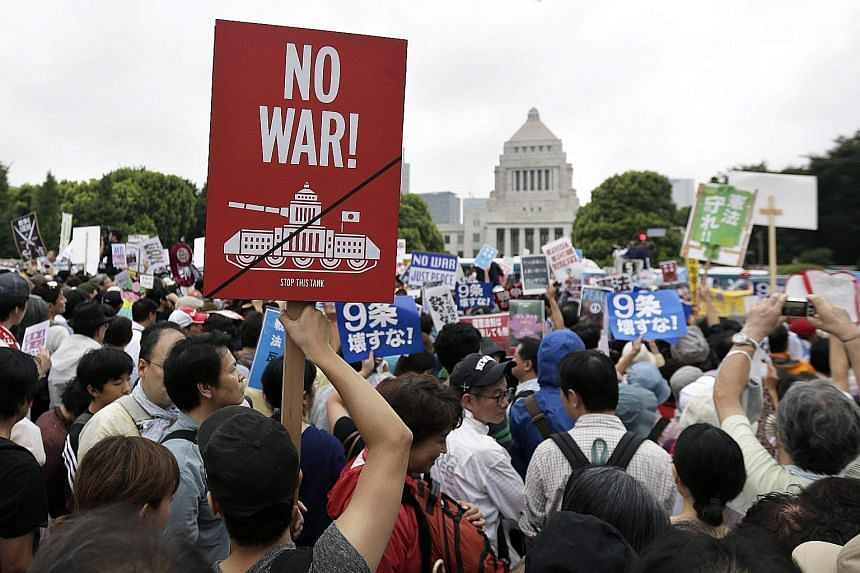 Demonstrators protesting against the controversial security Bills outside the Parliament in Tokyo yesterday. The rally was one of more than 300 held across Japan over the weekend.