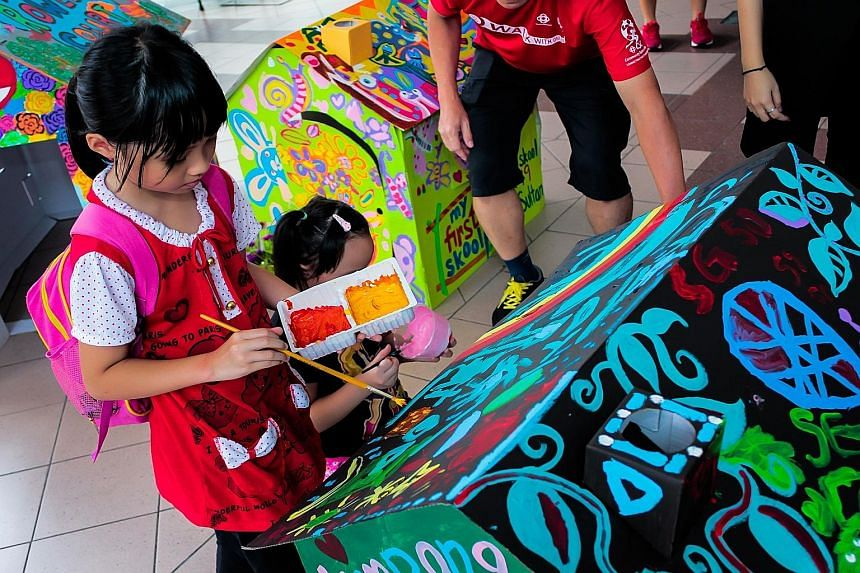 Nine-year-old Annabelle Wong painting one of the cardboard houses in the art installation at Kampong Glam Community Club.