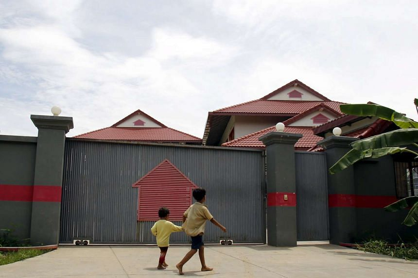 Boys walk in front of a house that is used to temporarily house asylum seekers sent from a South Pacific detention centre, in Phnom Penh, Cambodia on Aug 31, 2015.
