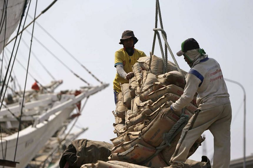 Workers arrange sacks of cement, which will be transported to Indonesia's Sumatra island, at Sunda Kelapa harbour in Jakarta, on Aug 26, 2015.