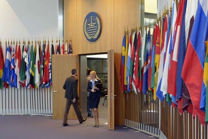 People walk past rows of flags at the main entrance of the courtroom of the International Tribunal for the Law of the Sea, in Hamburg, on Nov 6, 2013.