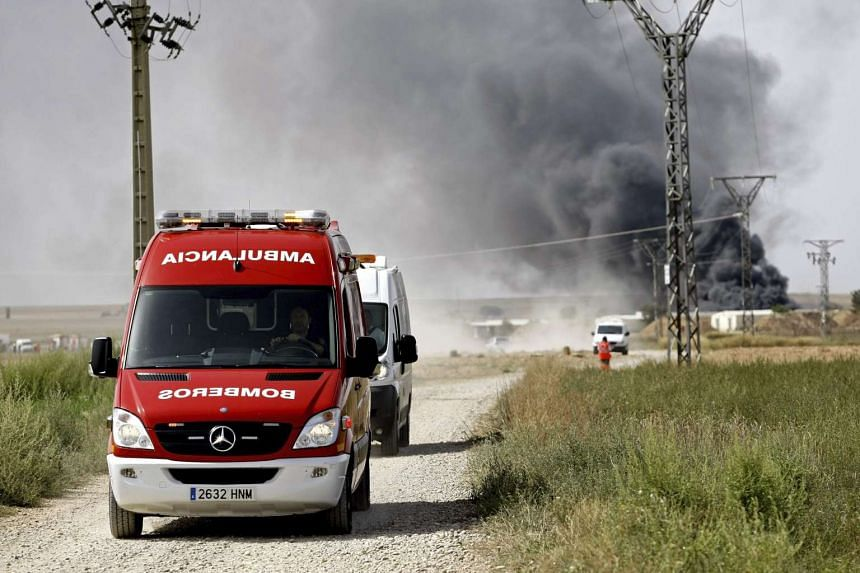 An ambulance is seen in the foreground as smoke rises from the Pirotecnia Zaragozana pyrotechnics company after an explosion, in Zaragoza, Spain, on Aug 31, 2015.