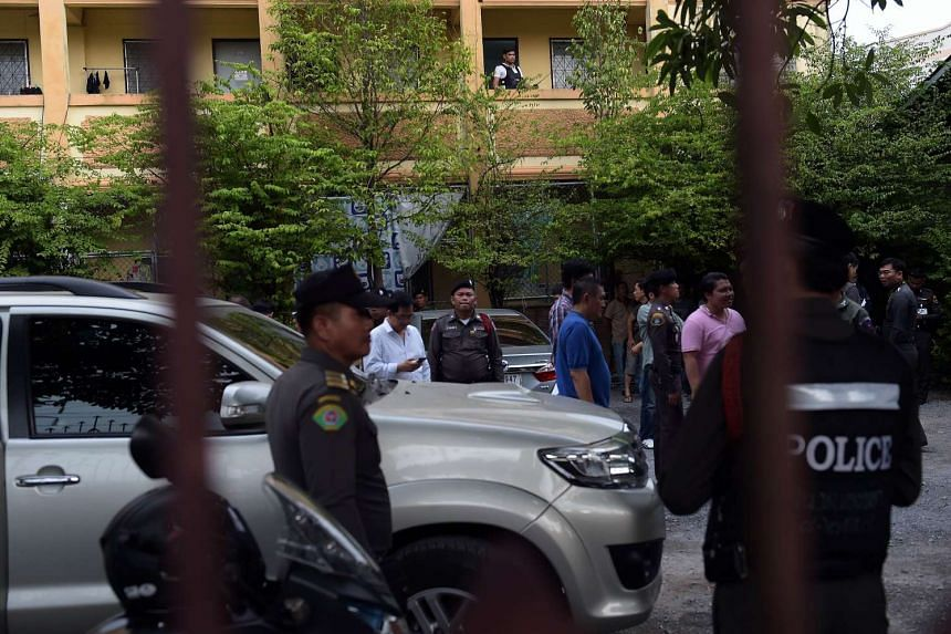 Policemen stand in the courtyard of the compound where they had detained a suspect in the Aug 17 Bangkok shrine bombing, in a Bangkok suburb on Aug 29, 2015.