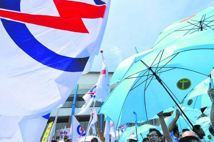 Supporters from the People's Action Party (PAP) (left) stand together with supporters from the Workers Party (WP) during Nomination Day on April 27, 2011.