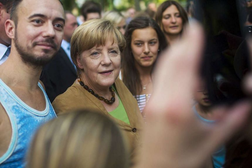 German Chancellor Angela Merkel poses with visitors at the Chancellery during the government's 'Open Door Day' in Berlin on Sunday.