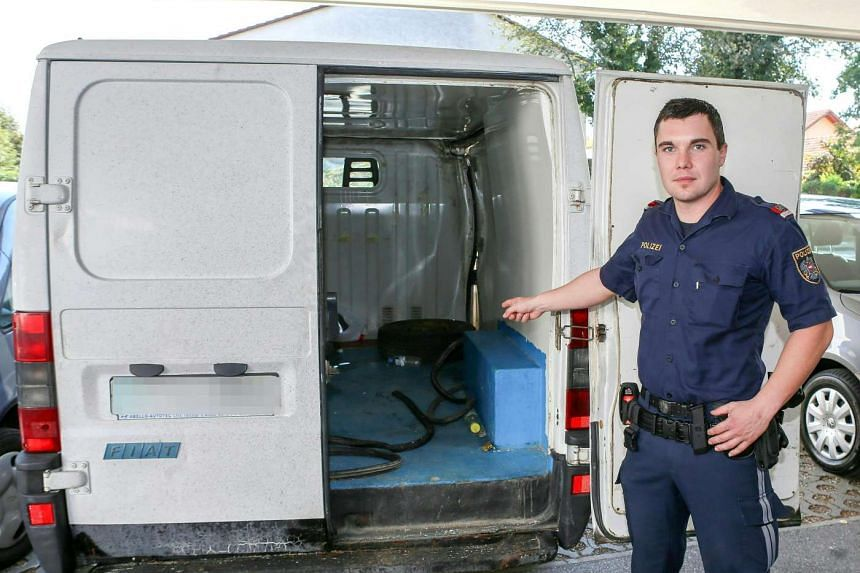 Inspector Jan Gieber of Austrian police shows the inside of the large van outside the police station in Braunau, Austria on Sunday. Three migrant children inside aged between 5 and 6 years were saved from dehydration by Austrian police on Friday. The