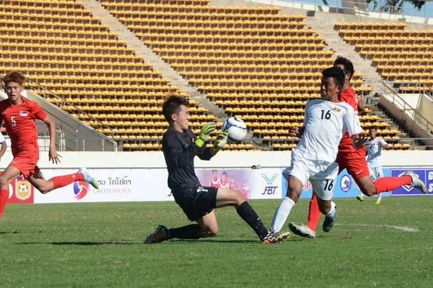 Singapore Under-19 goalkeeper Benedict Loh tries to get the ball ahead of Myanmar forward Aung Zin Phyo as Muhammad Shah (No. 5) looks on. Myanmar won 1-0.