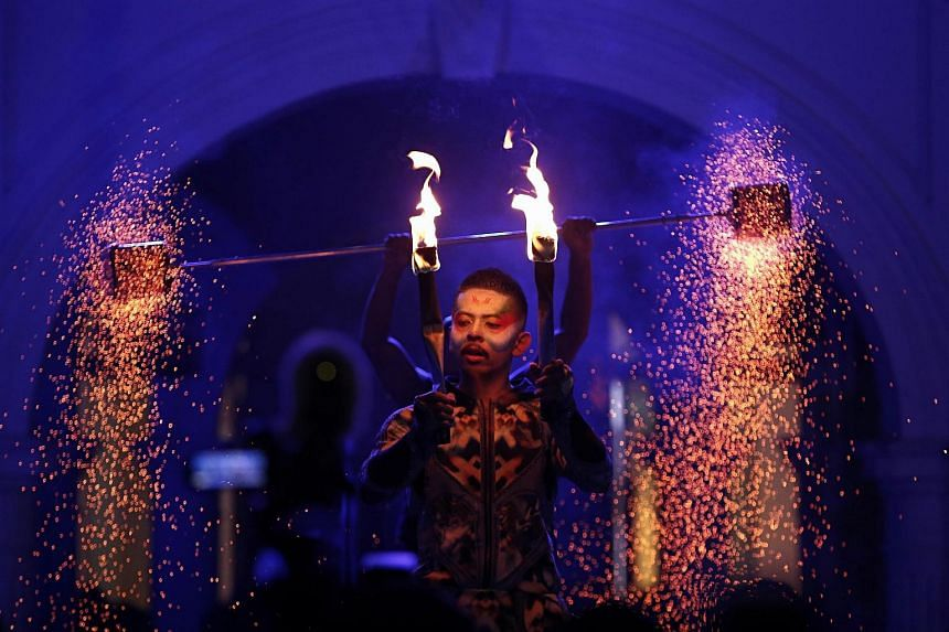 A artist performs with wielding flame torches 'The Garden of Fire & Light' during the Singapore Night Festival, in Singapore, on Aug 21, 2015.