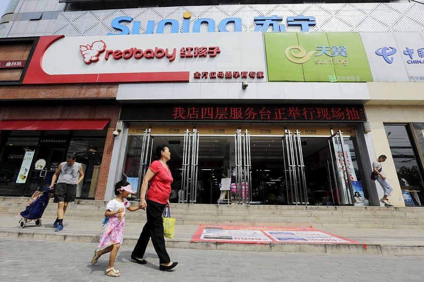 People walk past a Suning appliance store in Beijing, on Aug 11, 2015.