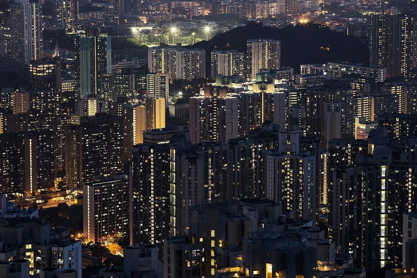Residential buildings stand illuminated at night in Hong Kong, China.