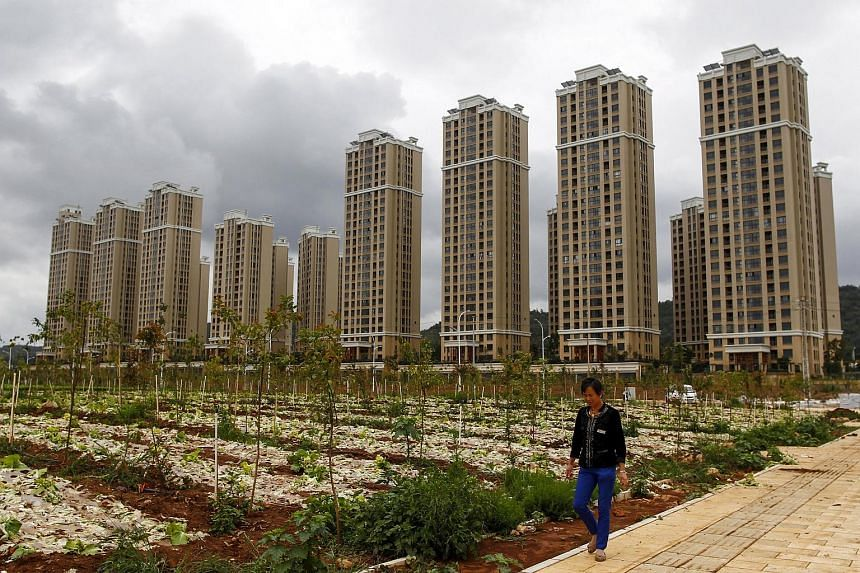 A farmer walks past a vegetable field next to newly-built residential buildings in Chenggong new district of Kunming, Yunnan province, China.