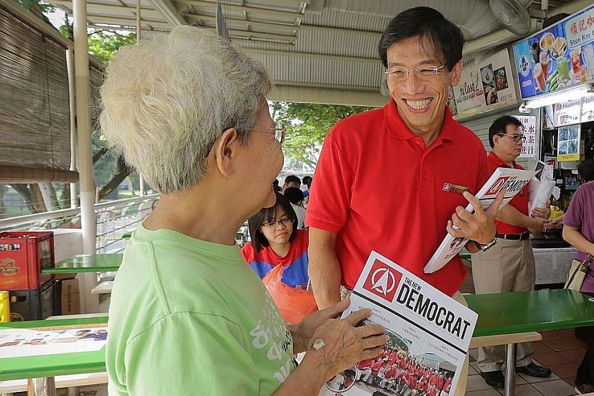 Dr Chee Soon Juan meeting a member of the public during his walkabout at Bukit Timah Market on Sunday. He says SDP aims to appeal to Singaporeans that it is important to have a competent opposition.